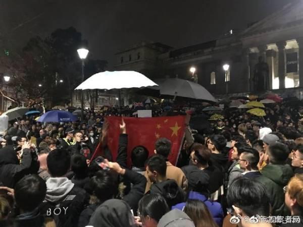"""中国留学生高唱国歌压制""""港独"""",冒雨为国旗撑伞"""
